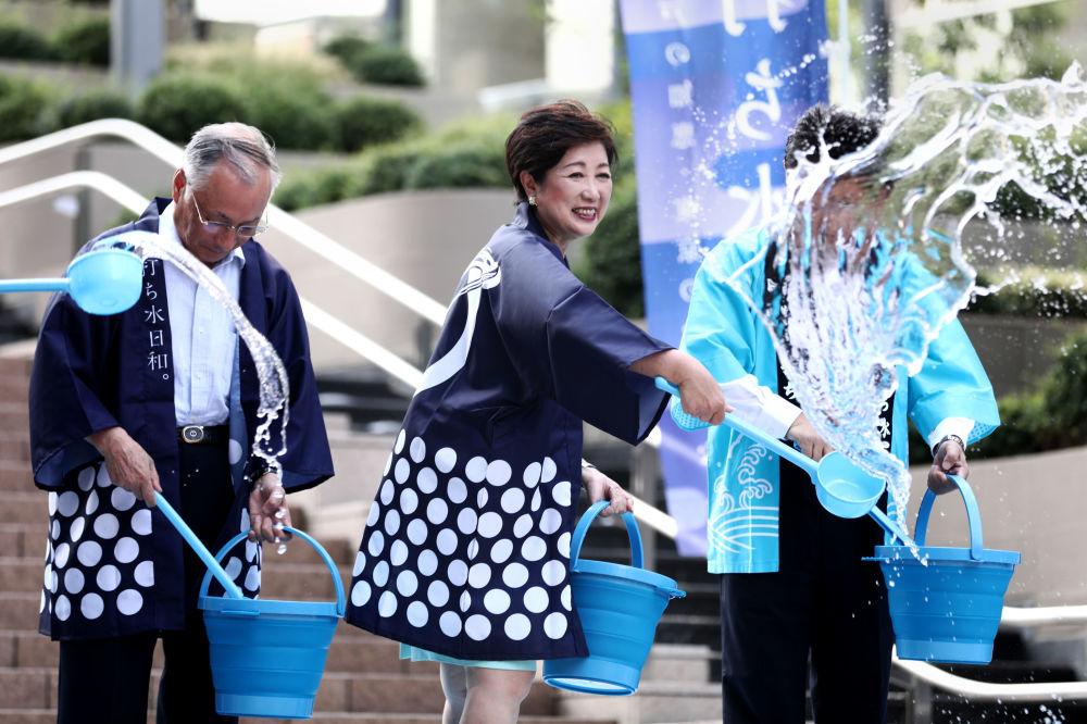 Gubernator Tokio Yuriko Koike polewa ziemię wodą podczas akcji ochładzania Tokio w dni anomalnego upału