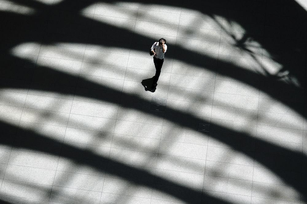Mężczyzna idzie w cieniu budynku podczas anomalnych upałów w Tokio
