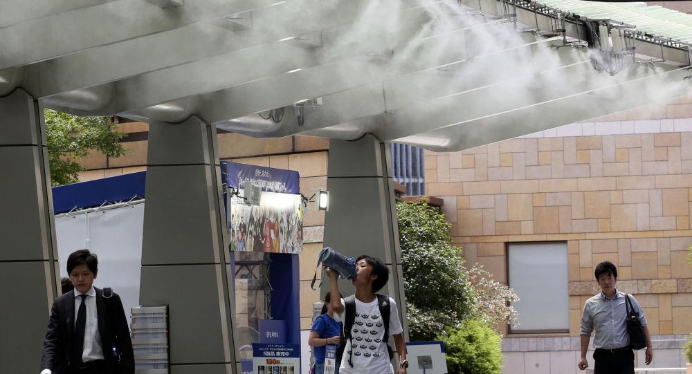 Ludzie pod ochładzającym urządzeniem podczas anomalnych upałów w Tokio
