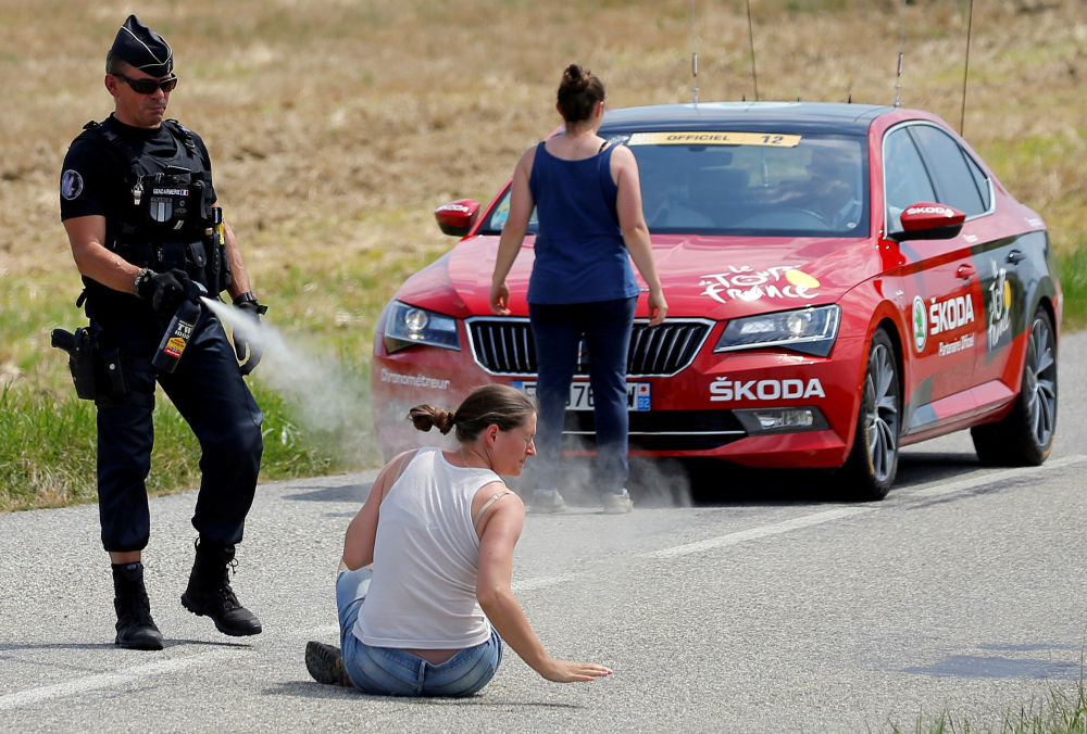 Policjant używa gazu pieprzowego przeciwko protestującej kobiecie podczas wyścigu kolarskiego Tour de France