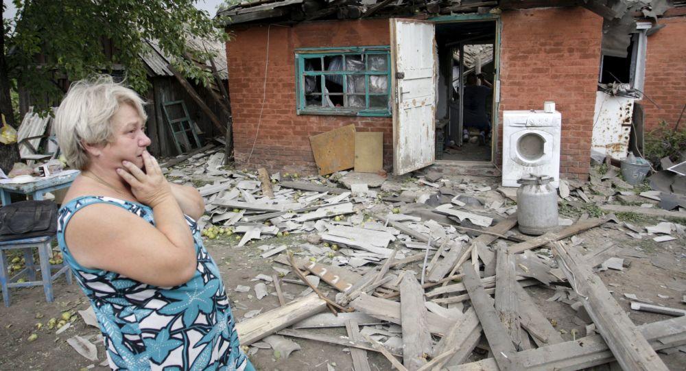 Kobieta obok swojego domu w Doniecku