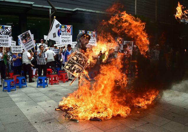 Południowi koreańczycy palą kukłę lidera Korei Północnej Kim Dzong Una podczas mitingu w Seulu