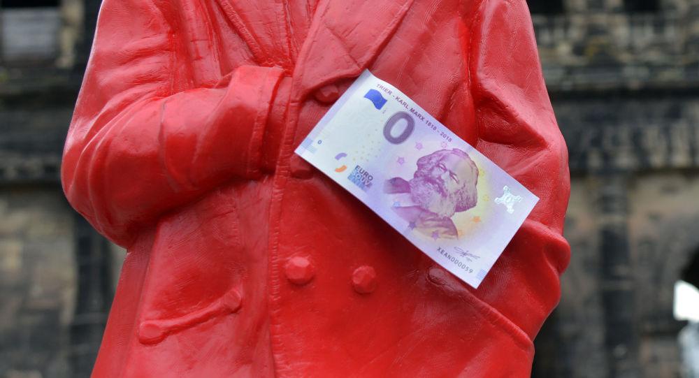 Banknot o nominale zero euro na czerwonej figurce Karola Marksa w Niemczech