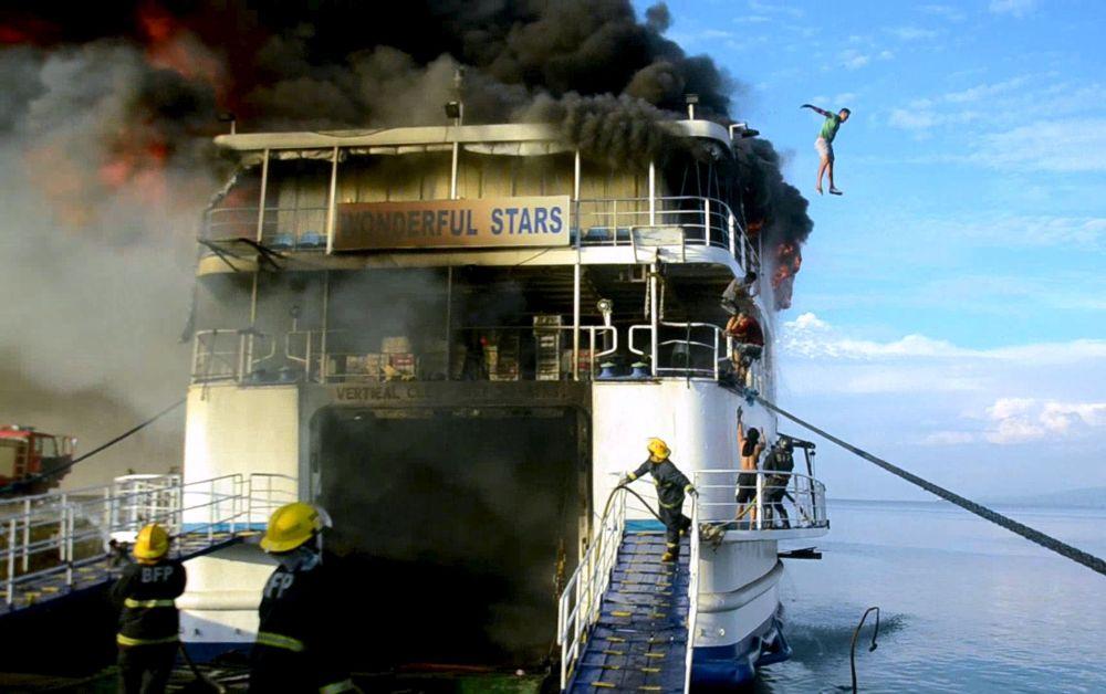 Członek załogi zeskakuje z płonącego statku MV Wonderful Stars przy brzegu Filipin