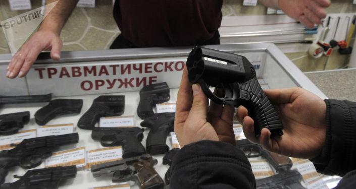 """Nabywca ogląda pistolet """"Osa"""" w jednym ze sklepów z bronią w Moskwie"""