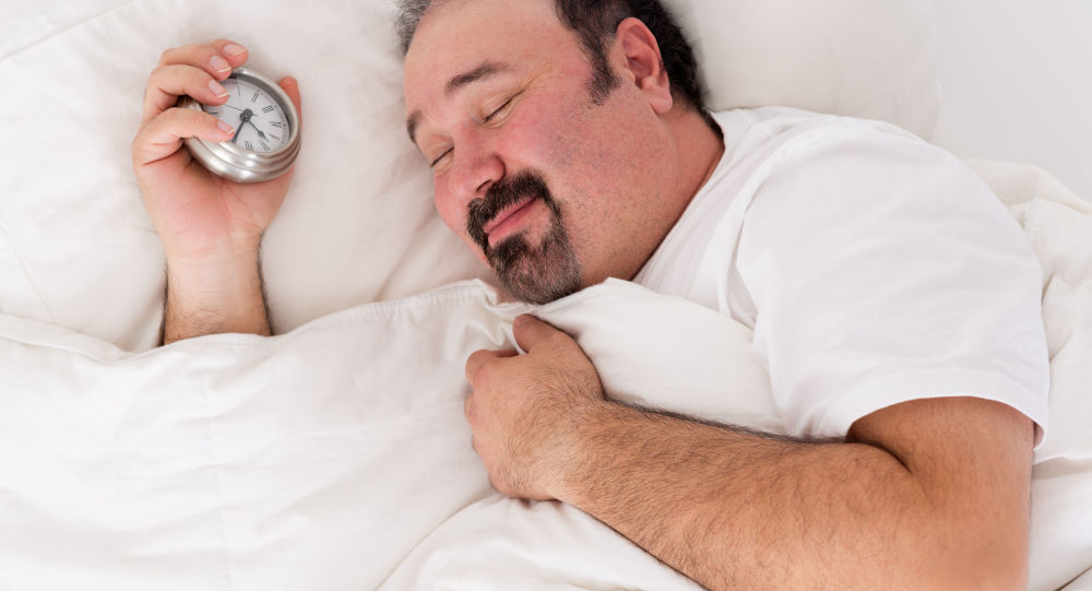 Śpiący mężczyzna z budzikiem