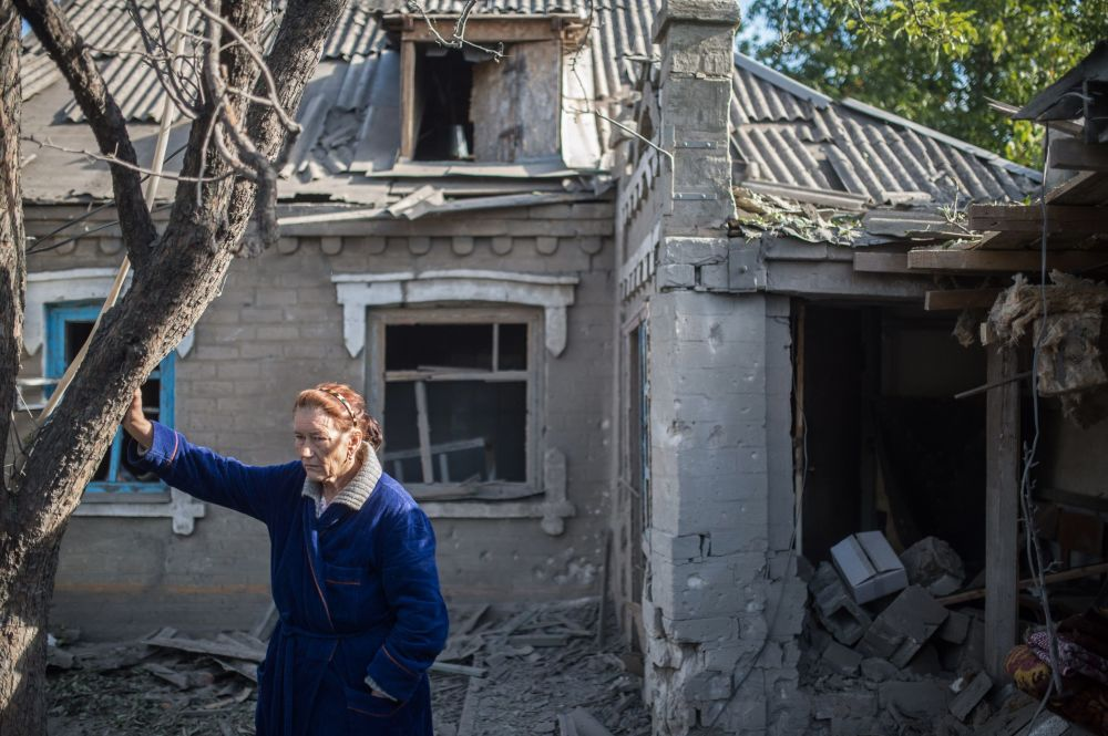 Kobieta przy zburzonym bloku w Aleksandrowce, obwód doniecki