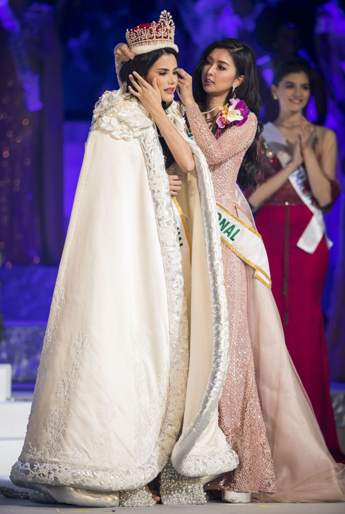"""Zwyciężczyni konkursu piękności """"Miss International – 2018"""" Mariem Claret Velazco Garcia z Wenezueli odbiera koronę od ubiegłorocznej zwyciężczyni  Kevin Liliany z Indonezji"""