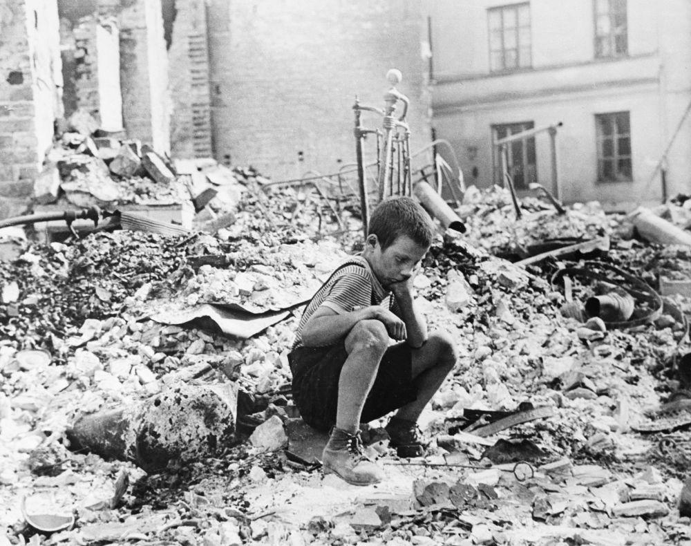 Chłopczyk siedzi na gruzach swojego domu w Polsce