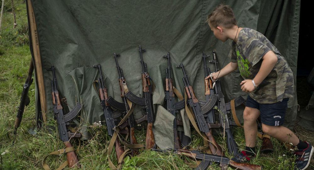 """Chłopiec obok karabinów AK-47 w letnim zmilitaryzowanym obozie dziecięcym """"Temper of will"""" zorganizowanej pod Tarnopolem na Ukrainie"""