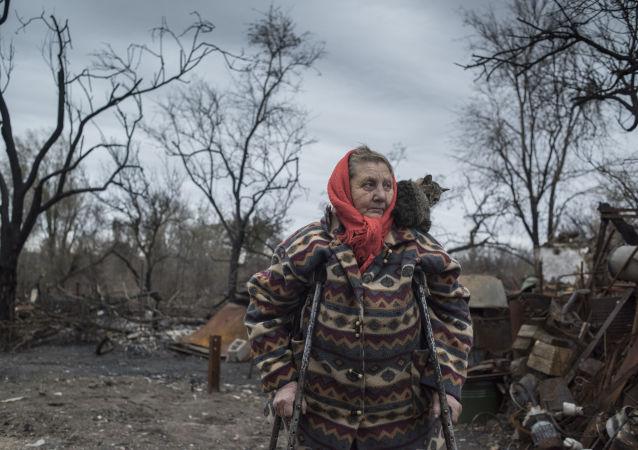 Kobieta stoi przed swoim zniszczonym domem w wiosce Sachanka pod Donieckiem