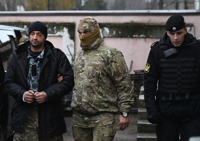"""Jeden z zatrzymanych marynarzy z okrętów Marynarki Wojennej Ukrainy """"Berdiańsk"""", """"Nikopol"""" i """"Jany Kapu"""" (po lewej) pod Sądem Rejonowym Symferopola, gdzie rozpatrywany jest wybór środka zapobiegawczego"""