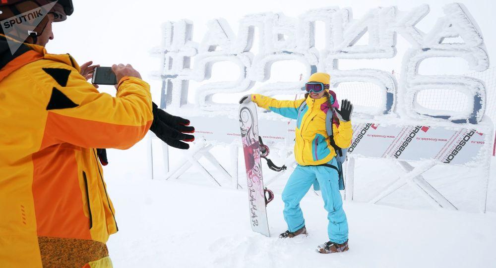 """Turyści fotografują się na tle napisu """"#Alpika 2256"""" w kurorcie górskim """"Gazprom"""" w Soczi"""