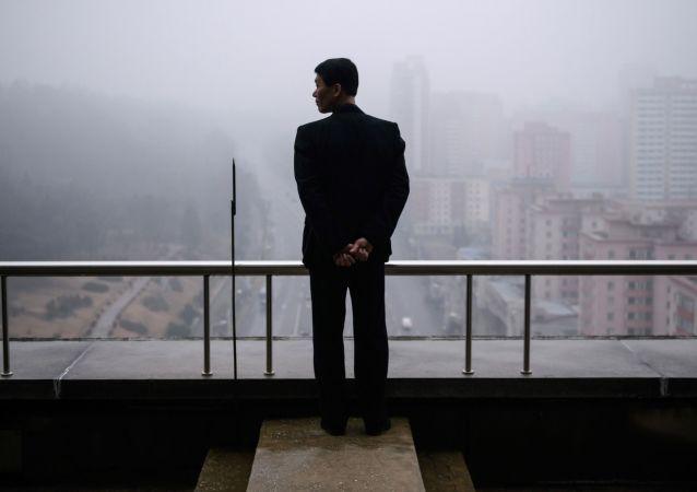 Mężczyzna na balkonie domu w Pjongjangu