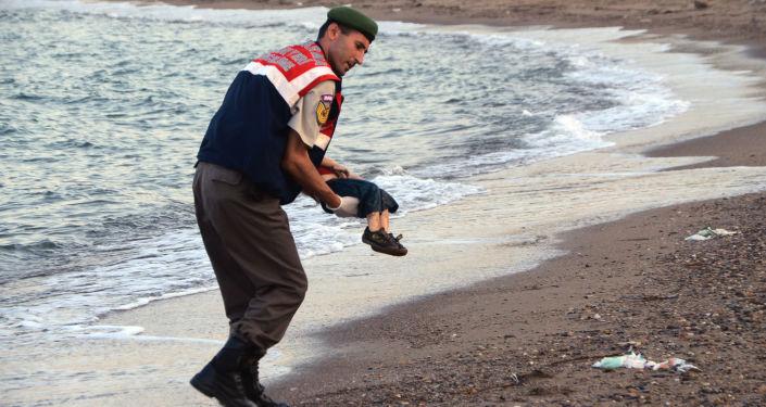 Policjant niesie ciało syryjskiego chłopca Aylana Kurdi