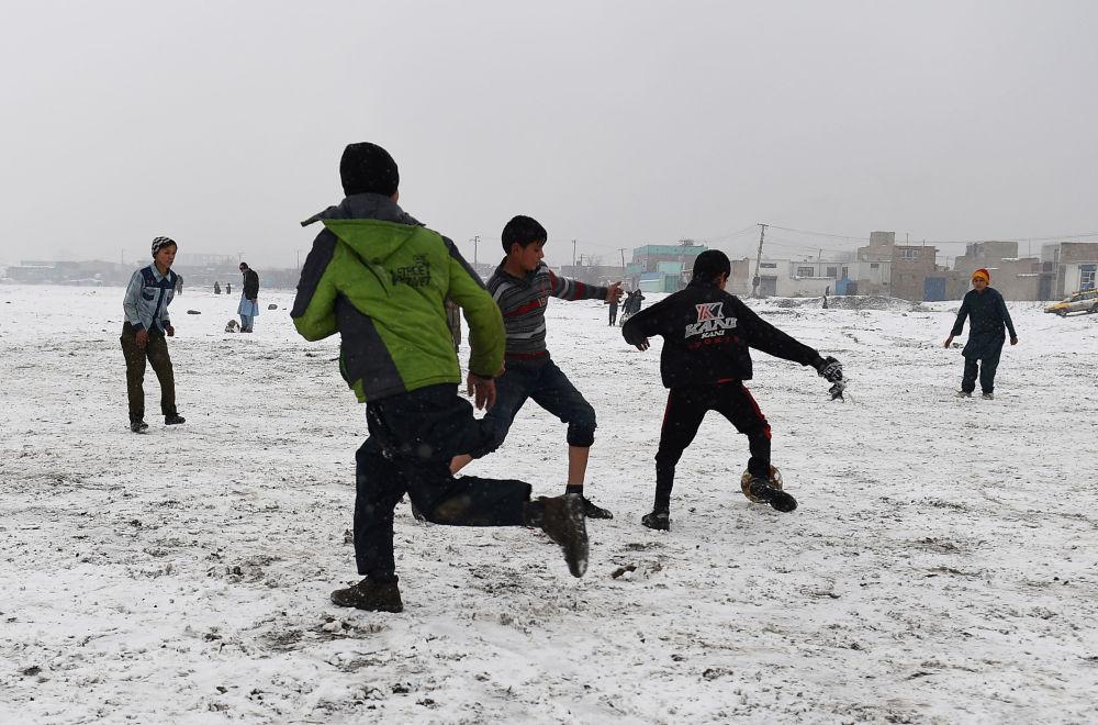 Dzieci grają w piłkę nożną po opadach śniegu w Kabulu