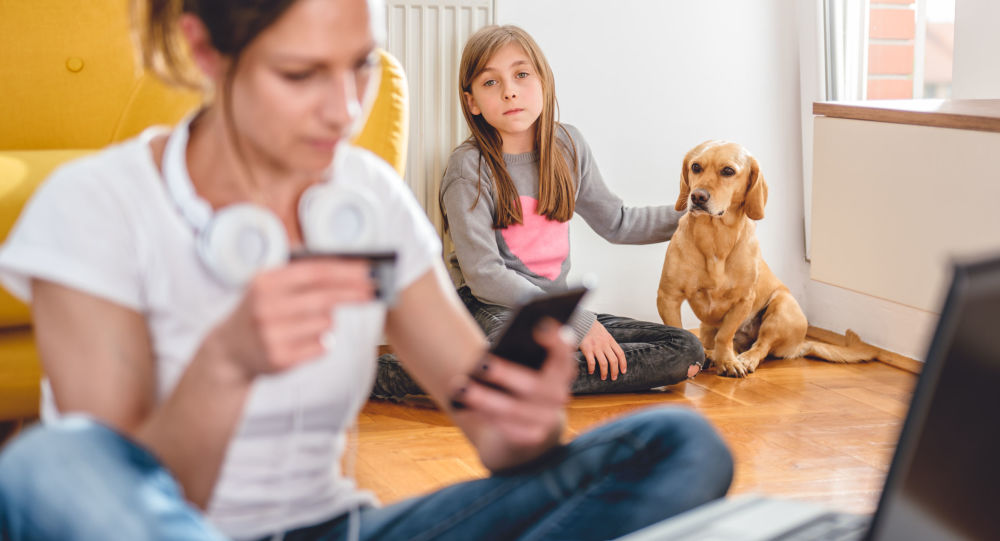Dziewczynka patrzy na mamę przed komputerem