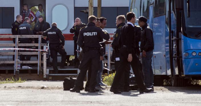 Oficerowie kontroli granicznej rejestrują uchodźców na granicy Danii i Niemiec