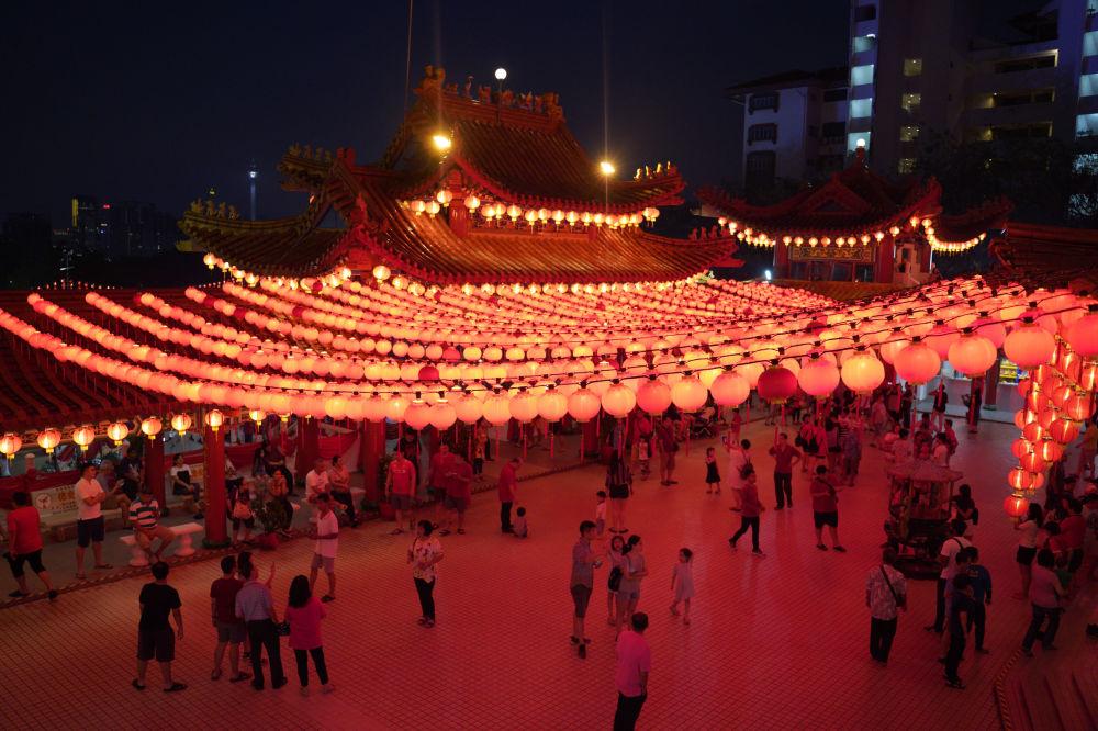 Uczestnicy obchodów Chińskiego Nowego Roku pod oświetleniem świątyni w Malezji