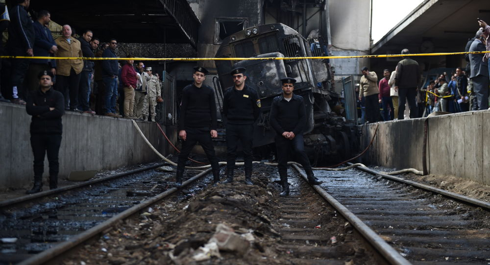 Funkcjonariusze policji na miejscu wypadku wokół spalonego pociągu w Kairze