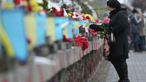 Kobieta składa kwiaty pod pomnikiem upamiętniającym ofiary protestów na Majdanie, do których doszło rok temu w Kijowie - Sputnik Polska