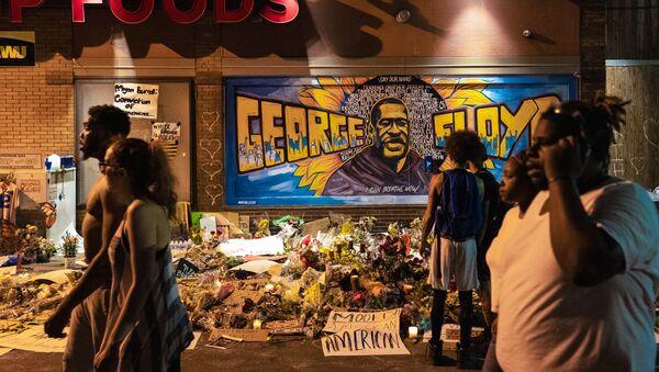 Kwiaty i świece na tle graffiti z portretem Afroamerykanina George'a Floyda na miejscu jego zabójstwa w Minneapolis w stanie Minnesota - Sputnik Polska