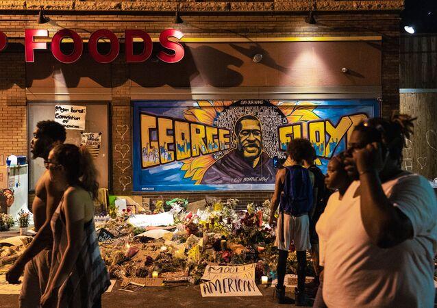 Kwiaty i świece na tle graffiti z portretem Afroamerykanina George'a Floyda na miejscu jego zabójstwa w Minneapolis w stanie Minnesota