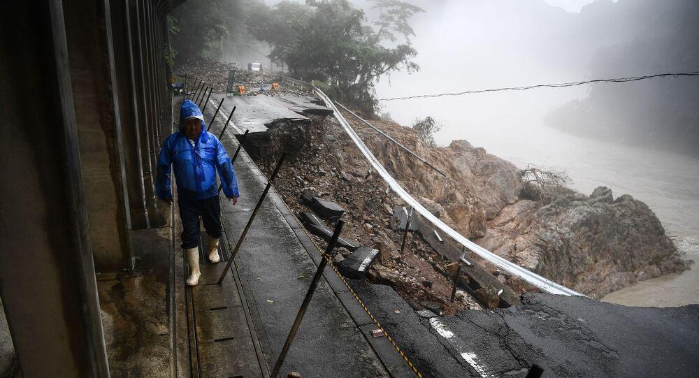 Mężczyzna idzie po zniszczonej przez osuwisko drodze.