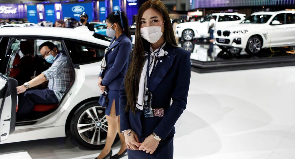 Dziewczyna w masce podczas targów motoryzacyjnych