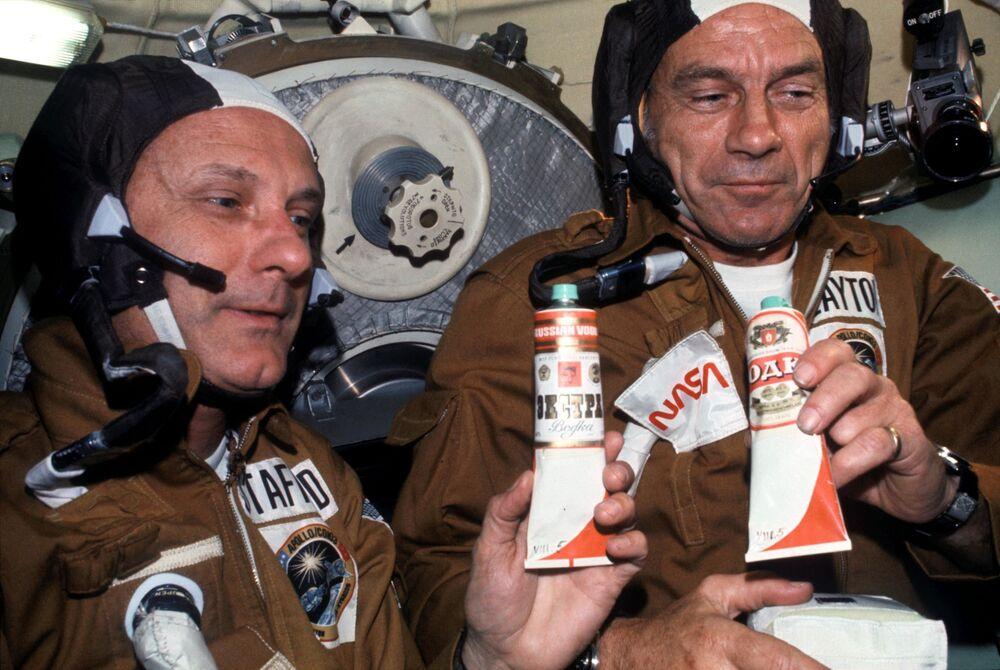 Astronauci Thomas P. Stafford i Donald K. Deke Slayton z tubkami barszczu i wódki po zadokowaniu statków Apollo-Sojuz