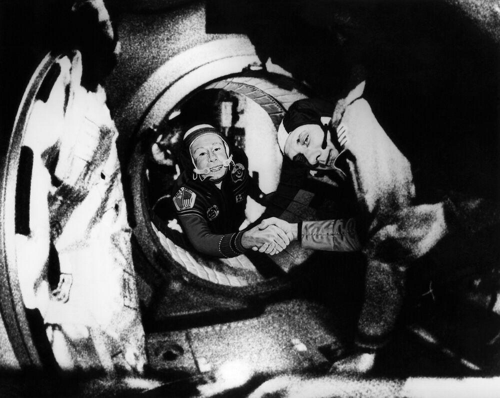 Pilot kosmonauta ZSRR Aleksiej Leonow i amerykański astronauta Thomas Patten Stafford ściskają sobie dłoń w ramach projektu pilotażowego Apollo-Sojuz