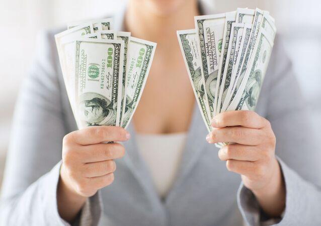 Kobieta trzyma dolary w rękach