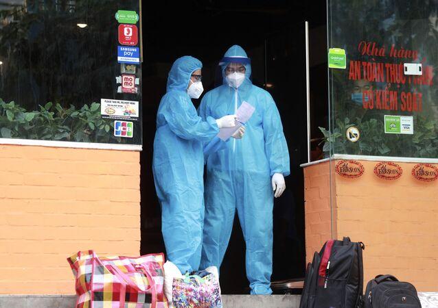 Pracownicy medyczni w restauracji w Hanoi, gdzie u pracownika podejrzewa się COVID-19, Wietnam