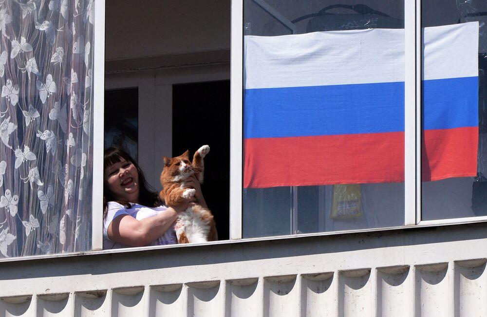 Mieszkanka Krasnojarska ze swoim kotem ogląda z okna swojego mieszkania występ zespołu muzycznego w Dzień Rosji