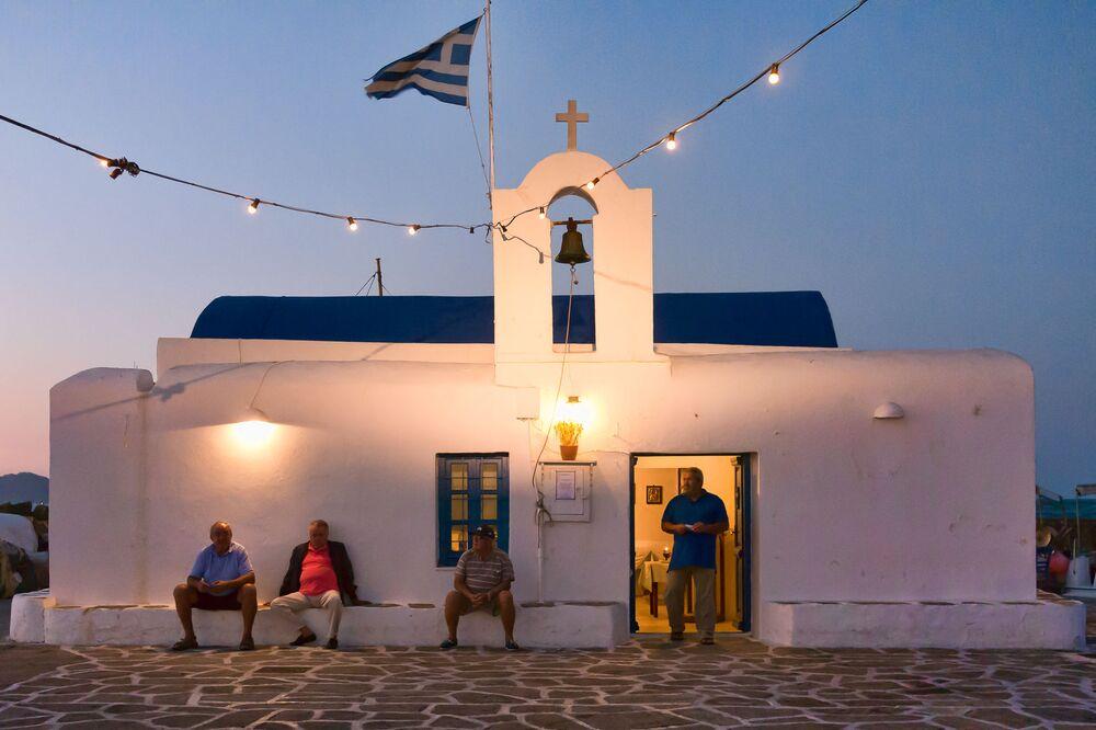 Rybacy przed kościołem w porcie Naousa w Grecji