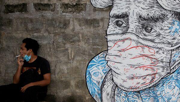 Mężczyzna pali papierosa obok graffiti z twarzą w masce, Manila, Filipiny - Sputnik Polska