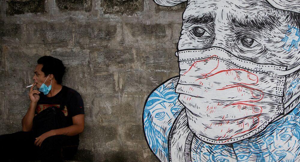 Mężczyzna pali papierosa obok graffiti z twarzą w masce, Manila, Filipiny