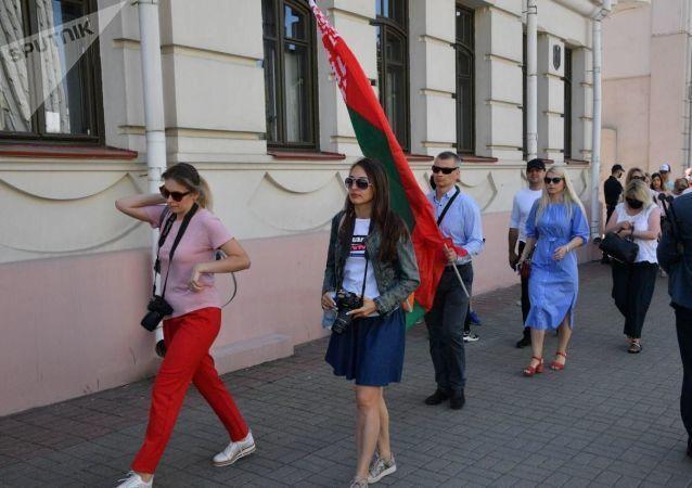 Uczestnicy mitingu przychodzą na Plac Niepodległości z flagami państwowymi.