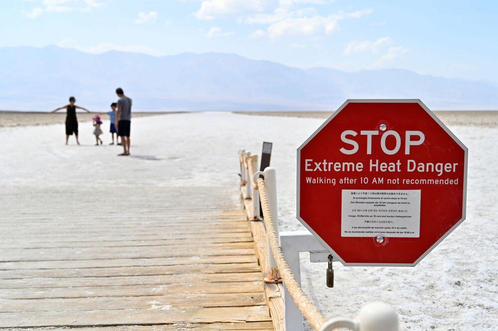 """Znak ostrzegający odwiedzających przed zagrożeniem ekstremalnych temperatur w basenie Badwater, najniższego punktu Ameryki Północnej – 279 stóp (85 m) poniżej poziomu morza w parku narodowym """"Dolina Śmierci"""", Kalifornia, USA."""