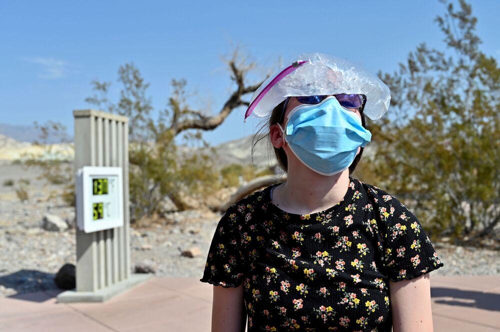 """Dziewczyna z torbą wypełnioną lodem na głowie w czasie wizyty w parku narodowym """"Dolina Śmierci"""", Kalifornia, USA."""