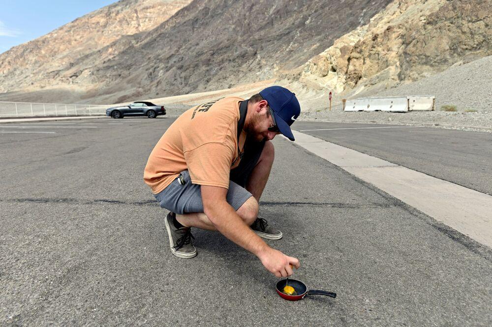 """Mężczyzna smaży jajecznicę przy drodze do parku """"Dolina Śmierci""""."""