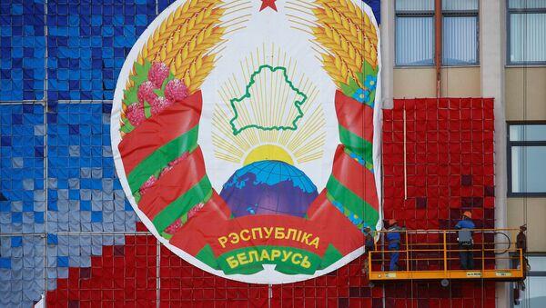 Białoruś 24 sierpnia 2020 r. robotnicy montują ogromny transparent z godłem państwowym Białorusi - Sputnik Polska