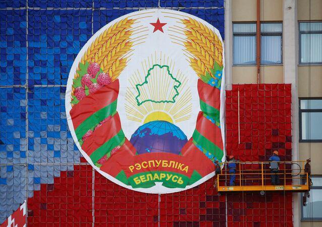 Białoruś 24 sierpnia 2020 r. robotnicy montują ogromny transparent z godłem państwowym Białorusi