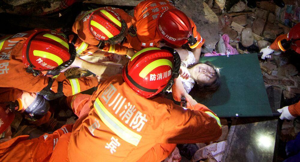 Ratownicy wyciągają spod gruzów kobietę po trzęsieniu ziemi, Chiny, 2019 r.