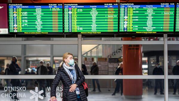 Pasażerowie w maseczkach na warszawskim lotnisku - Sputnik Polska