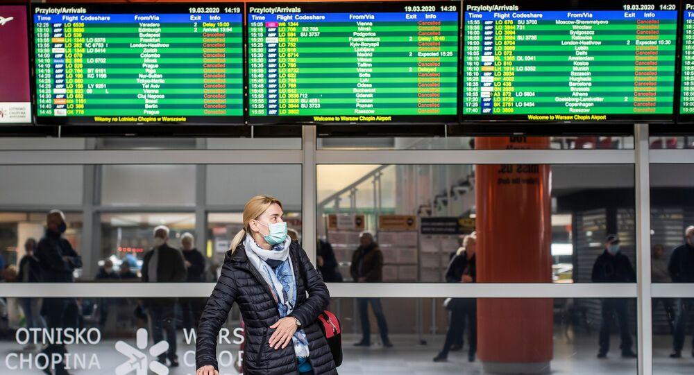 Pasażerowie w maseczkach na warszawskim lotnisku