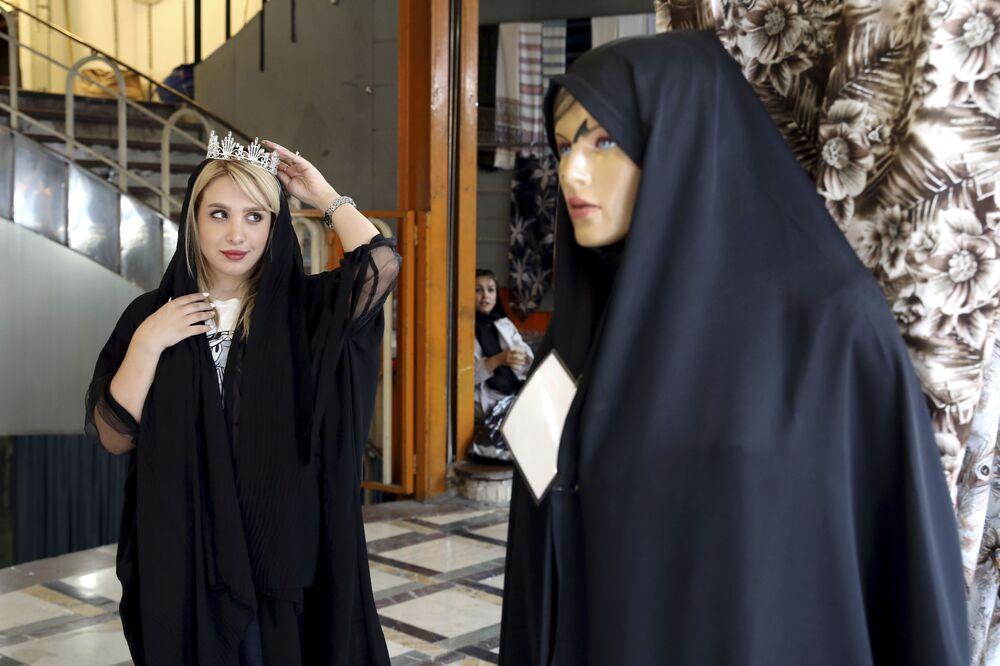 Dziewczyna przymierza koronę w sklepie w Teheranie