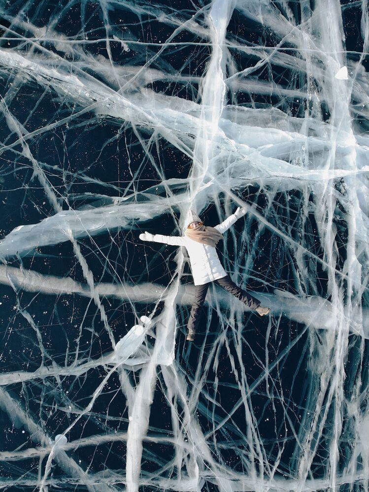 Dziewczyna leży na lodzie zamarzniętego Bajkału