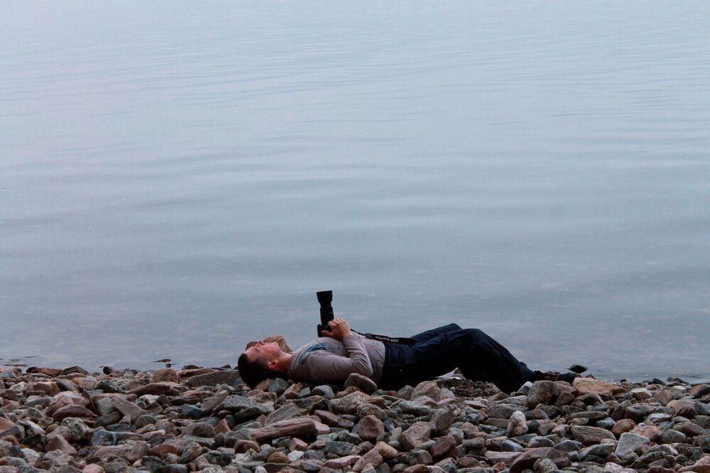 Fotograf z aparatem na brzegu Bajkału
