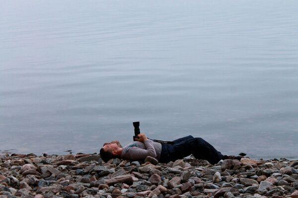 Fotograf z aparatem na brzegu Bajkału - Sputnik Polska